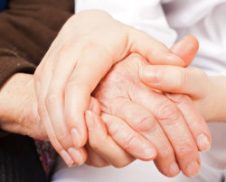 caregiver holding the hands of elderly