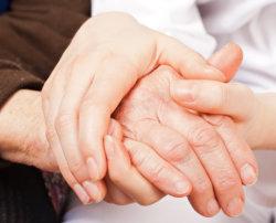 caregiver holding the hands of elderly