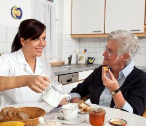 caretaker is preparing meal for her patient