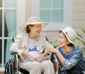 senior women relax on wheelchair in backyard with her caregiver