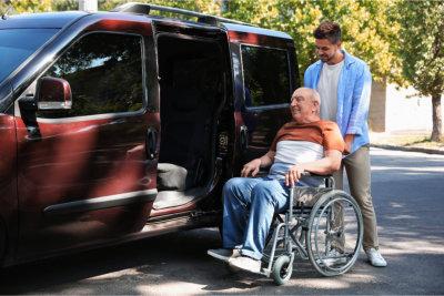 Young men helping patient in wheelchair to get into van outdoors
